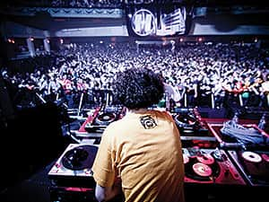 The back of a DJ in a yellow shirt, performing to a packed crowd in a club
