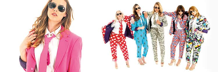 A close up of a woman in a pink blazer and white shirt, and five women in Opposuits