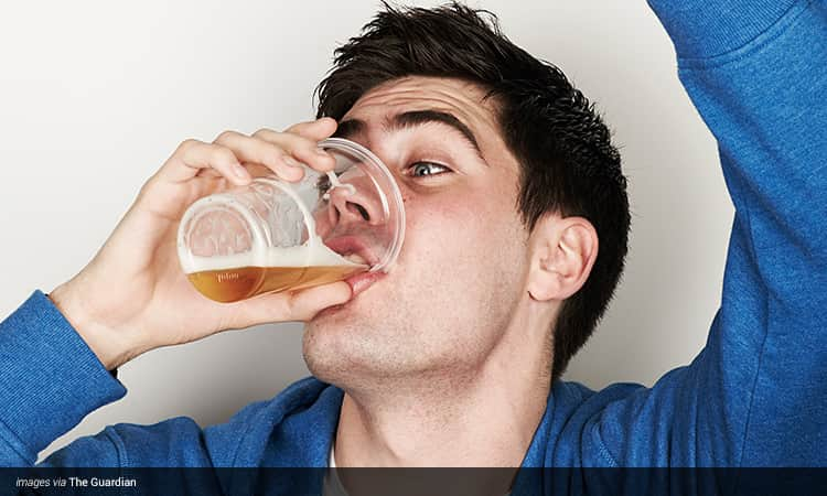 Man downing a beer from a plastic cup