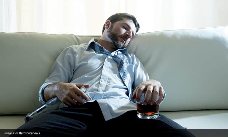 Man asleep on the sofa with a glass of whiskey in one hand and a bottle in the other