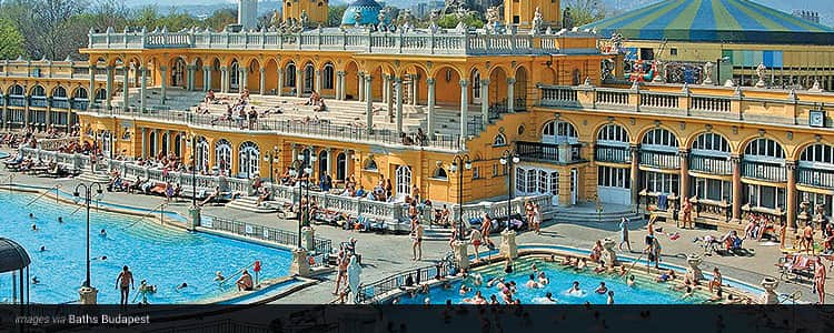 The yellow exterior and outdoor pool of the Turkish Baths, Budapest, with people standing outside of the building and in the pool