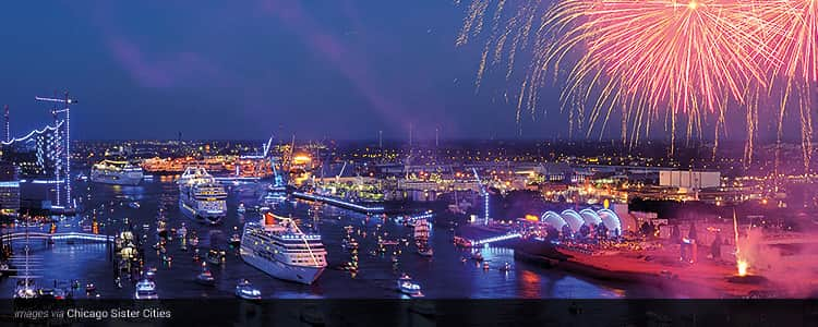 The marina of Hamburg at night, filled with boats and with pink fireworks exploding in the sky