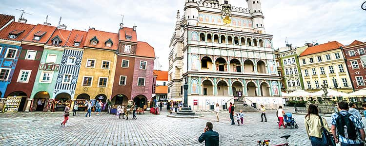 The Renaissance Town Hall in Poznan and the colourful buildings in the Old Town centre, with people in the foreground