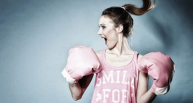 A woman in a pink vest, and pink boxing gloves jumping and screaming