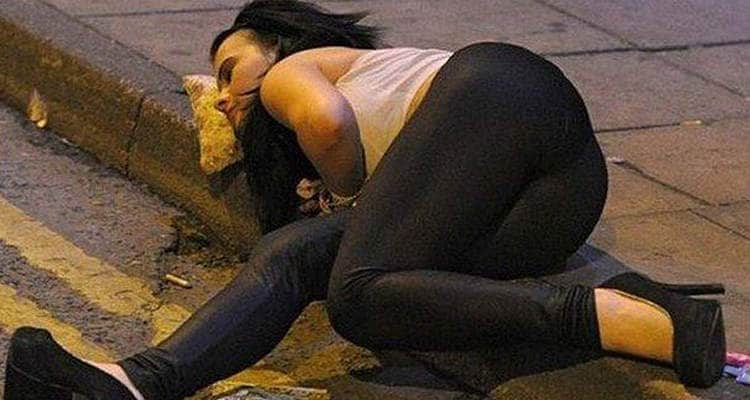 A woman lying on a pizza slice on the pavement