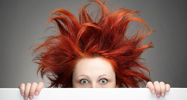 A woman with messy red hair looking over a white wall, with a close up on her face