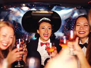 A woman in a red bow tie and tiara, sat amongst her friends in a car and drinking champagne