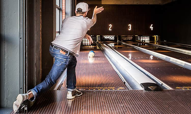 A man bowling a ball down the alley at the pins