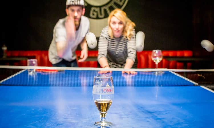 A girl and a boy attempting to bounce ping pong balls into a glass of beer