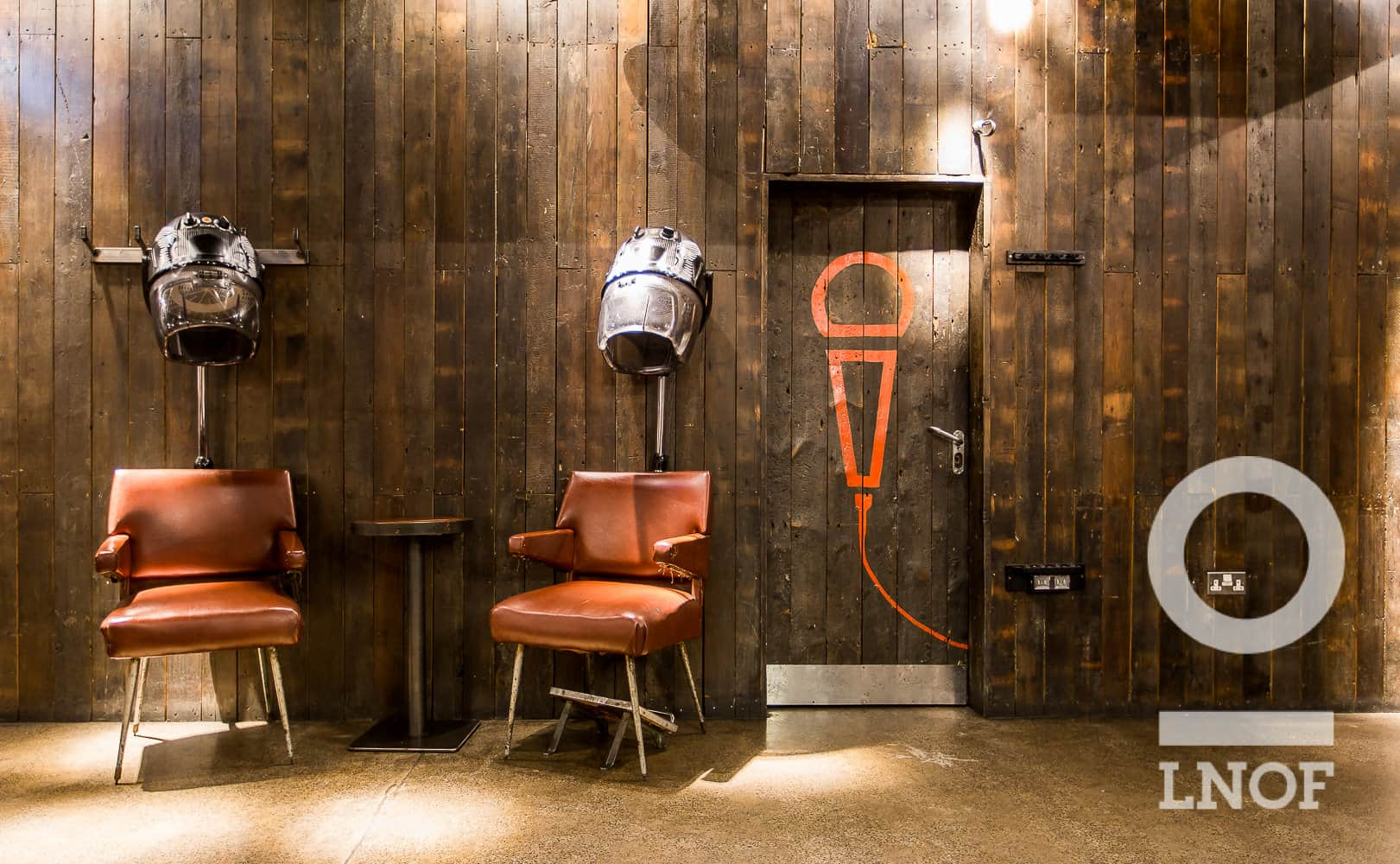 Two chairs with old fashioned hairdryers above, and a door with a microphone on