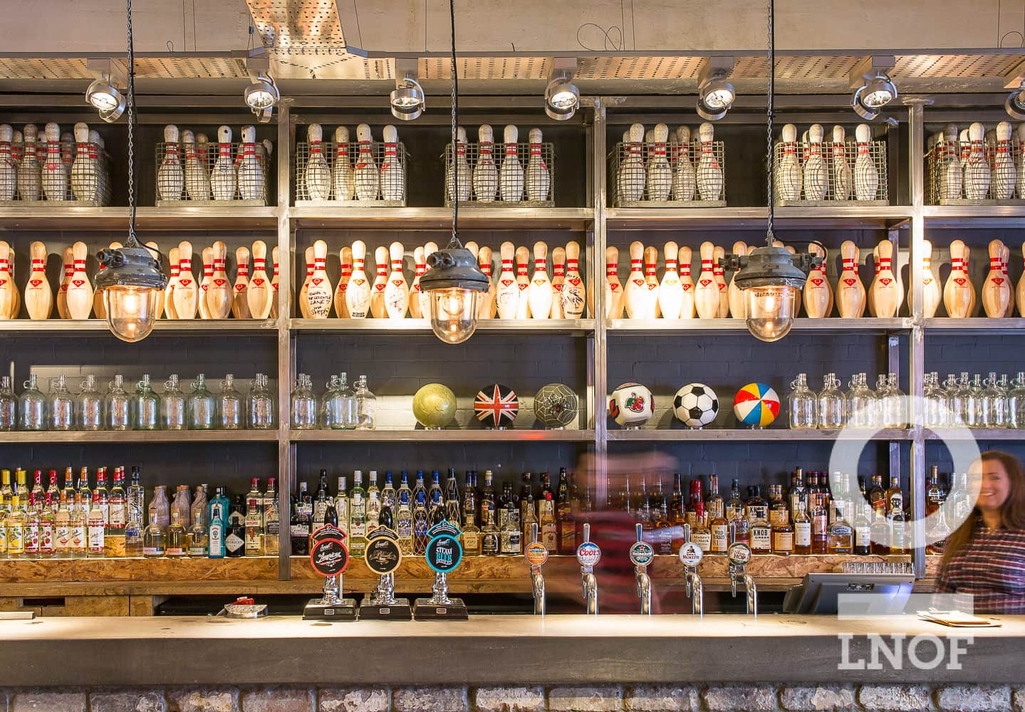 The bar in Lane7 with bowling pins and alcohol on the shelves