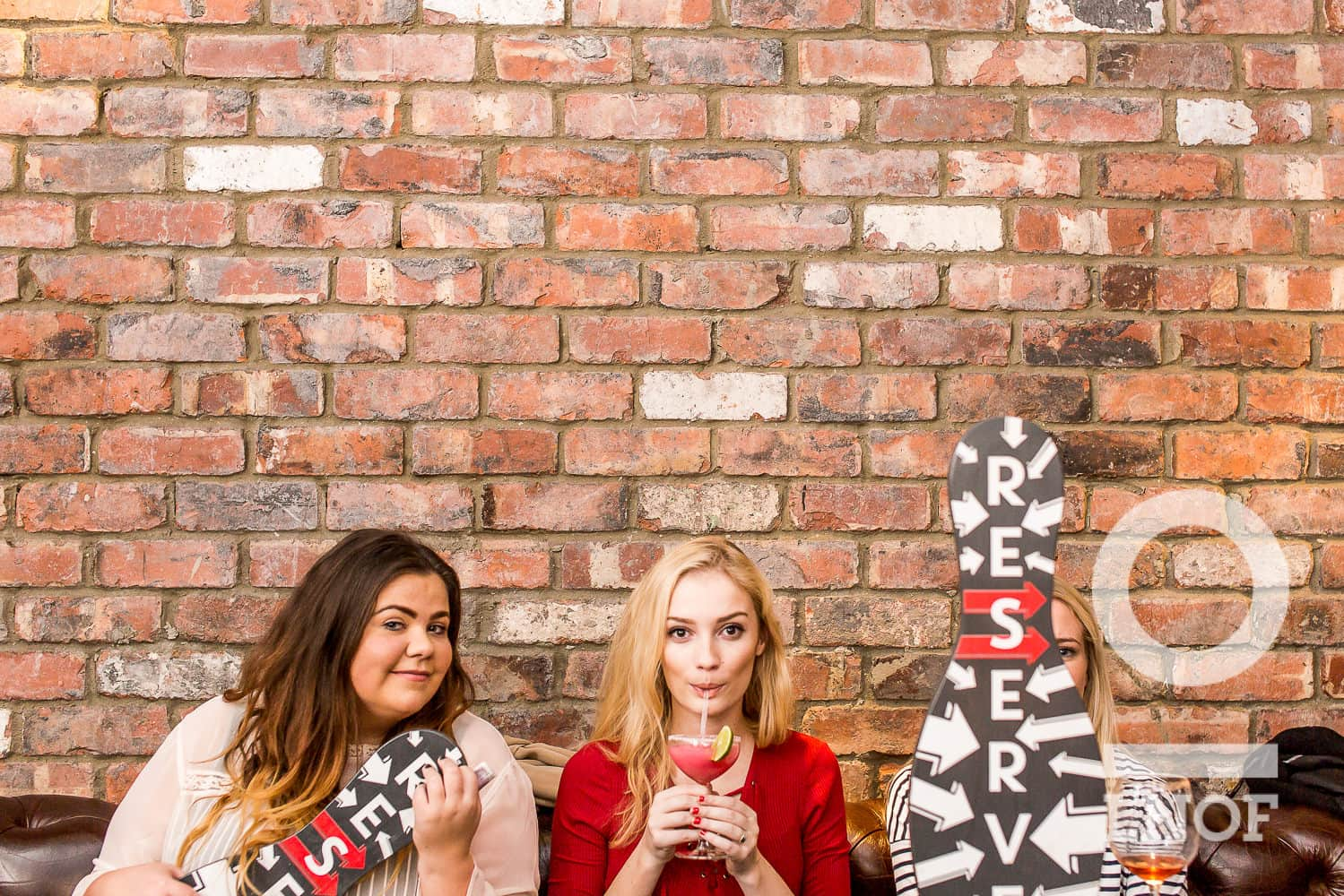 Three girls sitting, one covered by a wooden bowling pin, in front of an exposed brick wall
