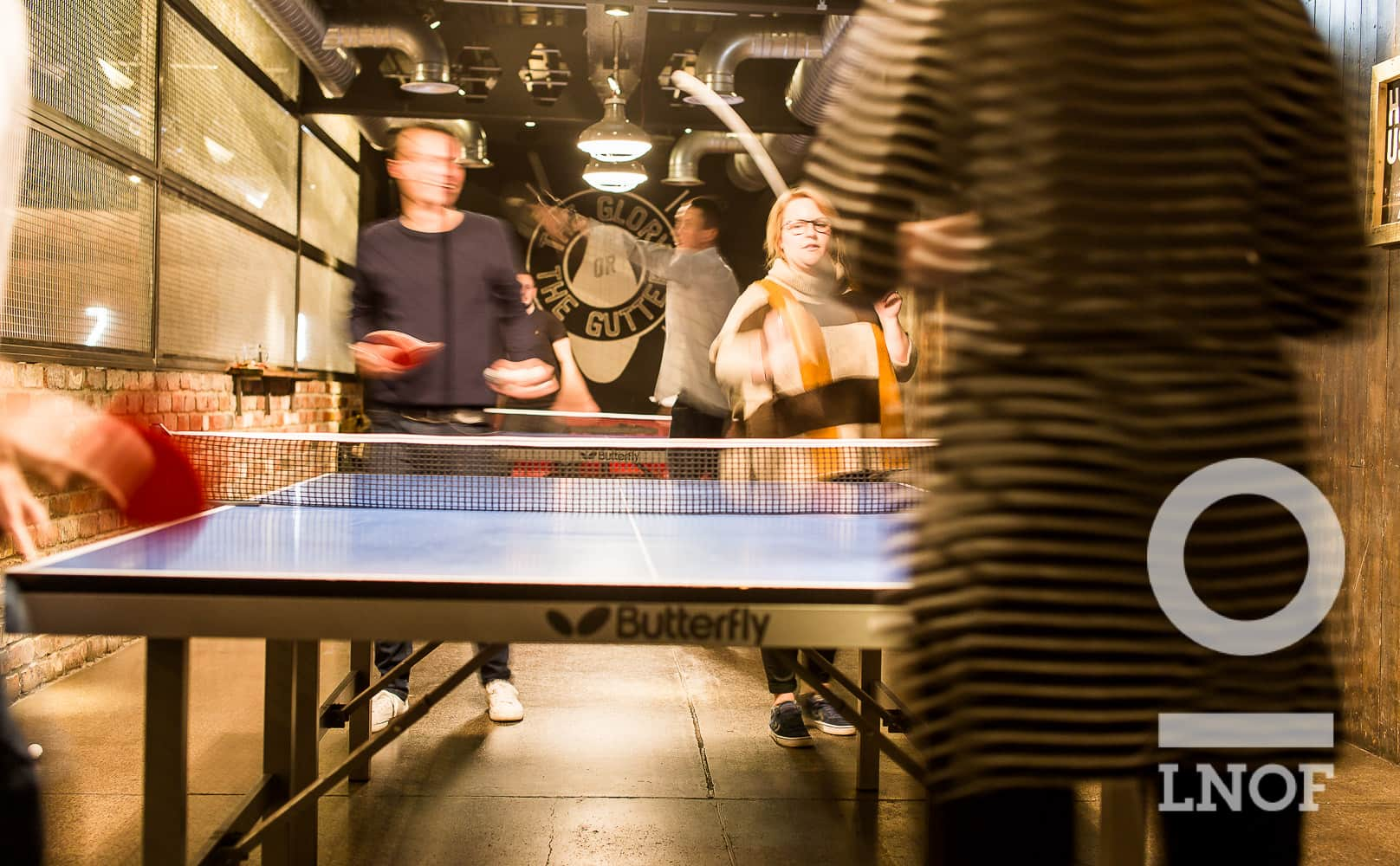 Four young people playing ping pong