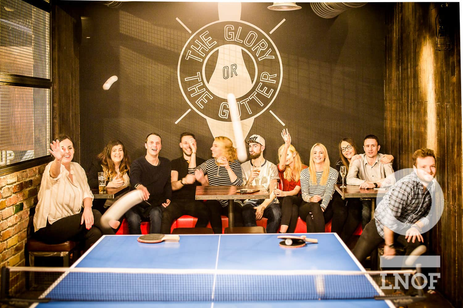 A group of young people throwing ping pong balls at the camera