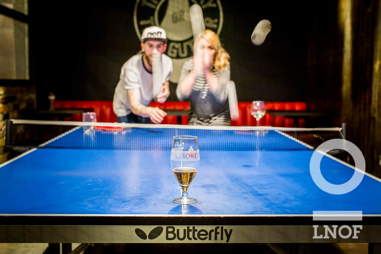 A boy and a girl bouncing ping pong balls on a ping pong table, aiming for a beer glass