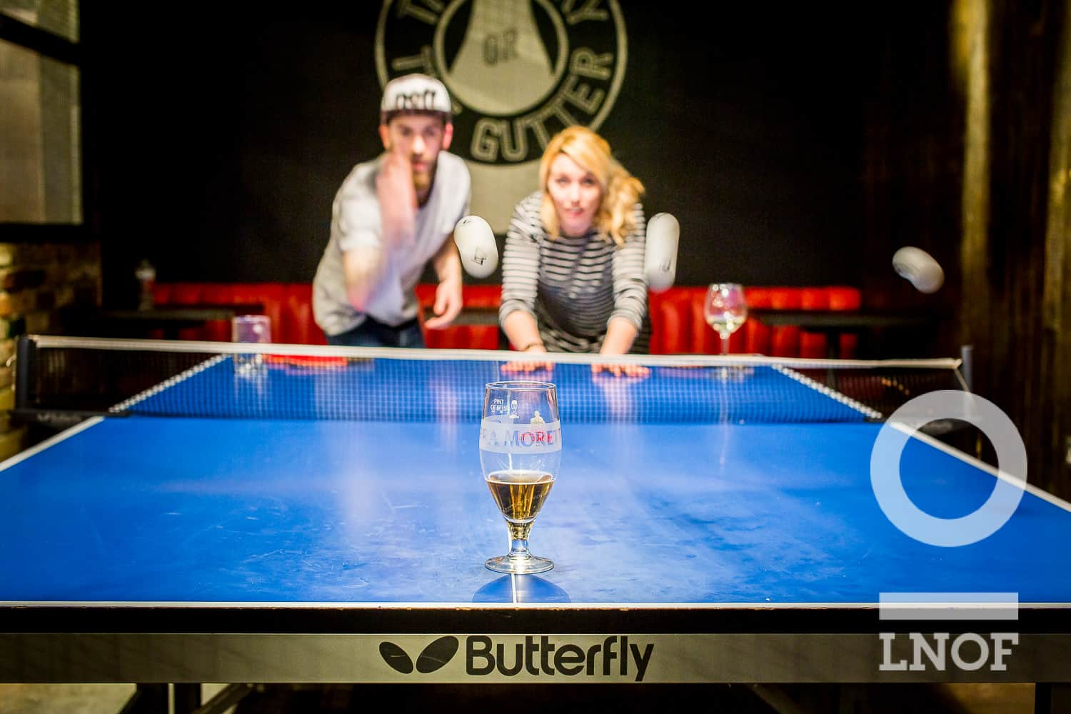 A boy and a girl attempting to bounce ping pong balls into a beer glass