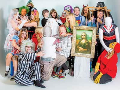 An image of people in Halloween costumes posing in a white studio