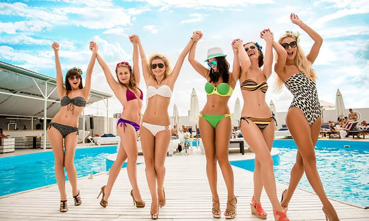 Women in bikinis, posing with a pool in the background