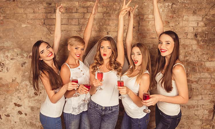 Women in white vests and jeans, posing with their hands in the air and with wine glasses