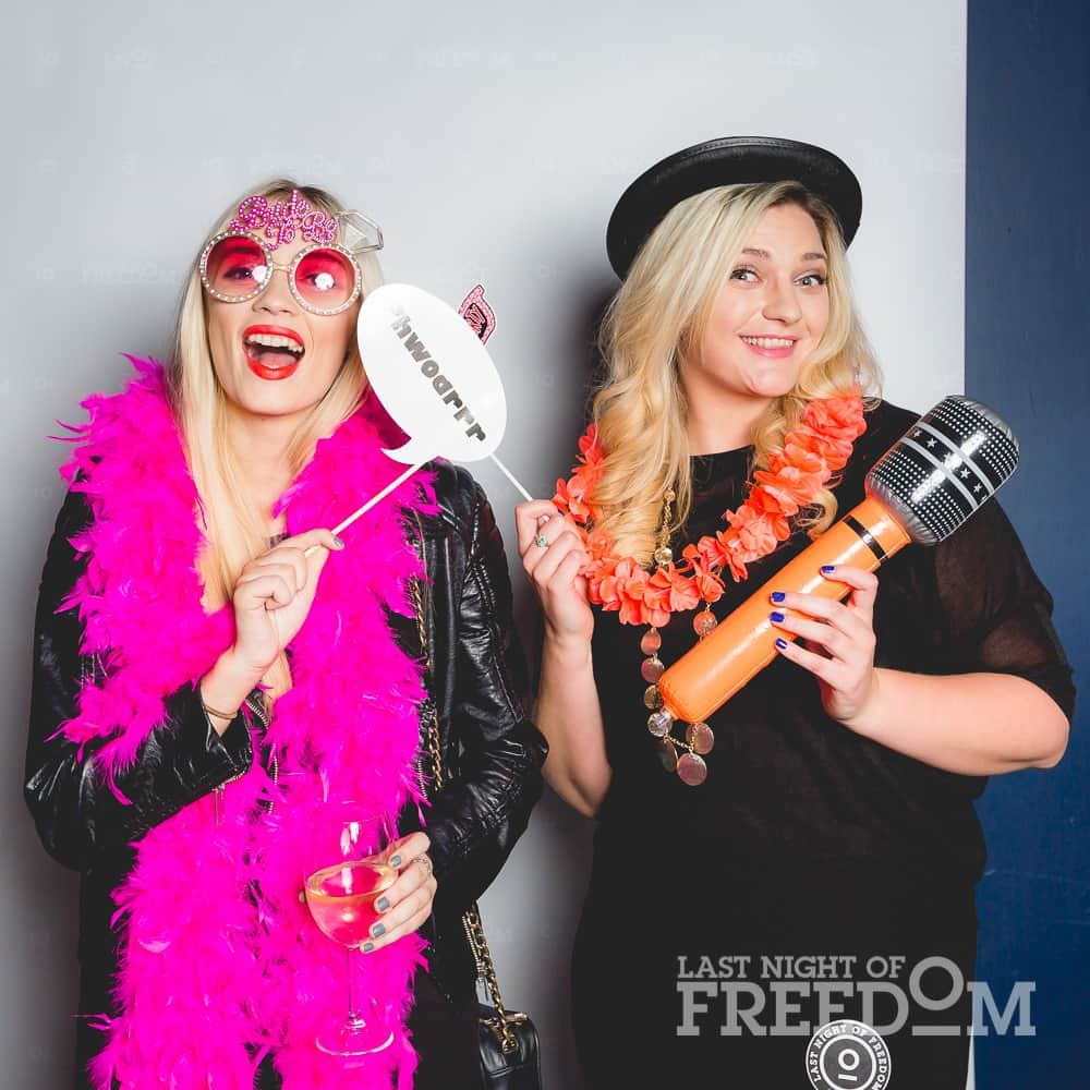 Two women posing in a photobooth with props