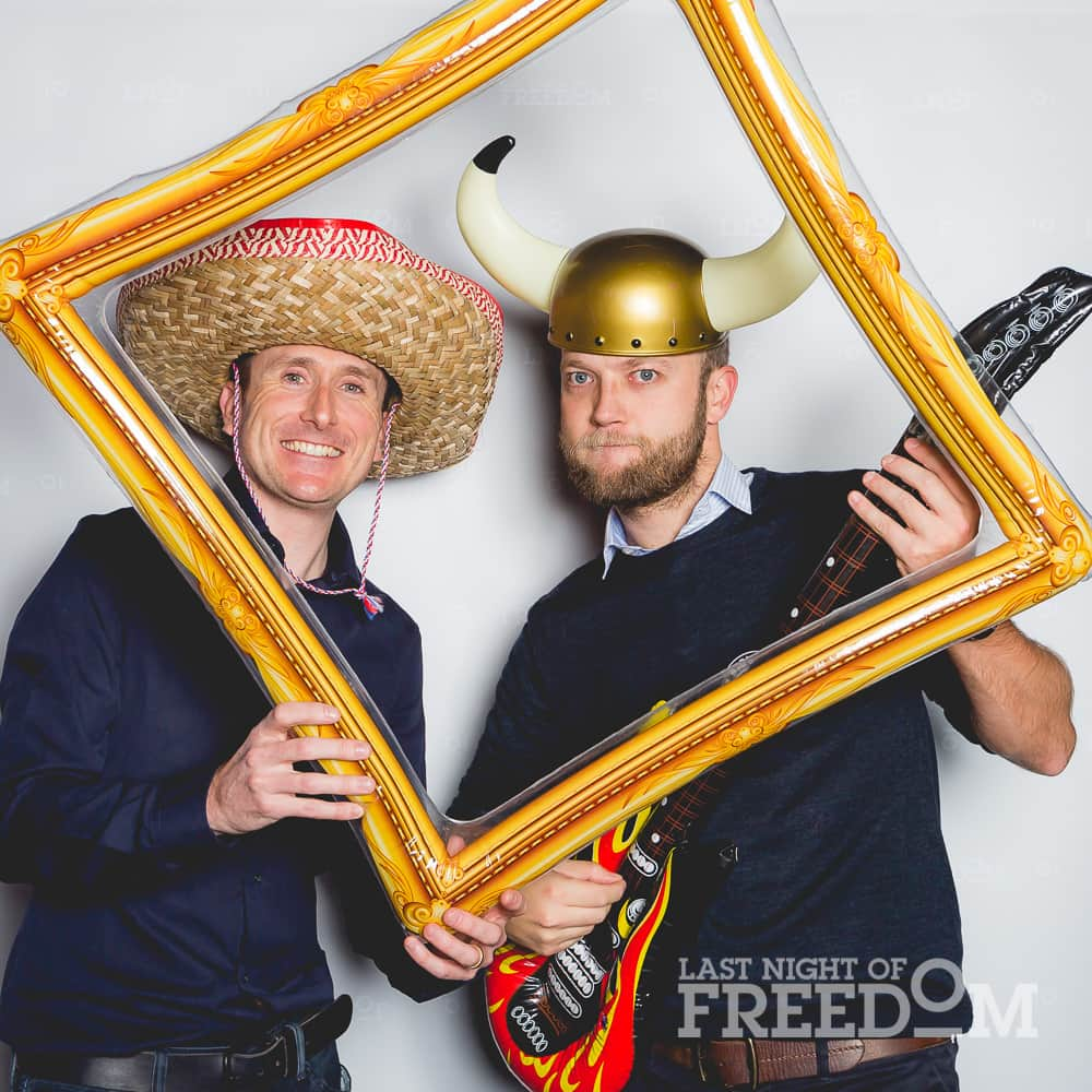 Two men posing in a photobooth with accessories whilst holding a fake photo frame
