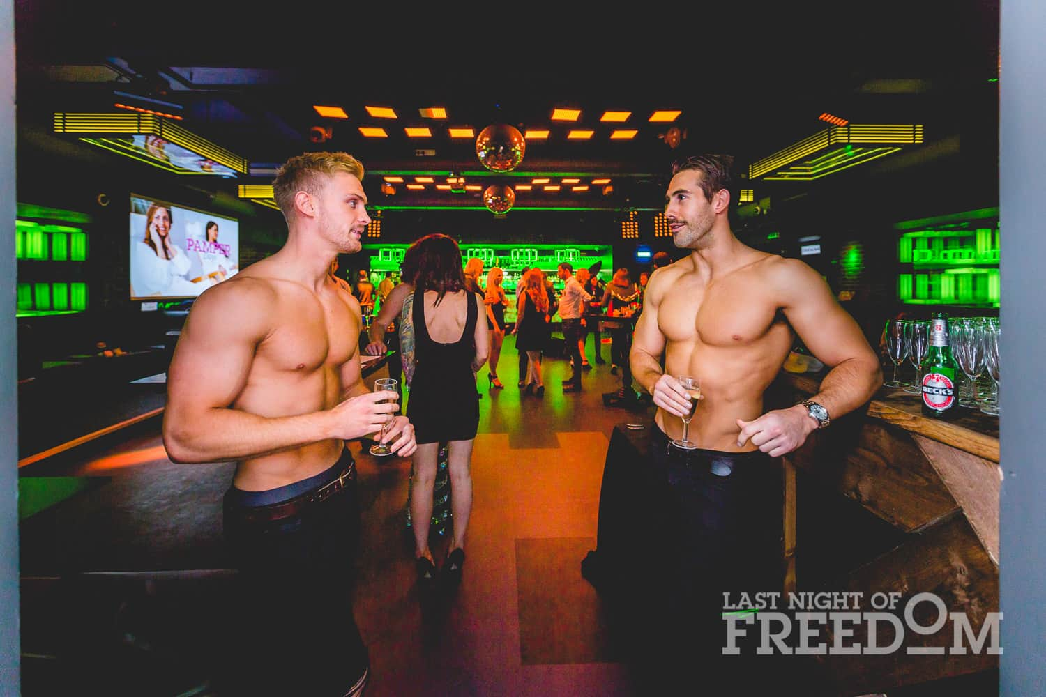 Two semi-naked men chatting in a bar, with other people stood around in the background
