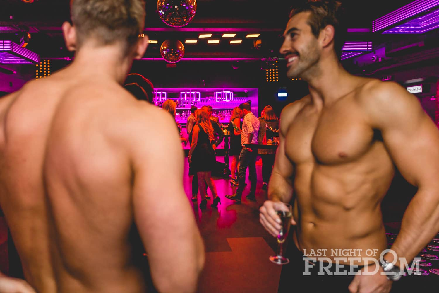 Close up of two semi-naked men chatting, with people in the background to a backdrop of pink light