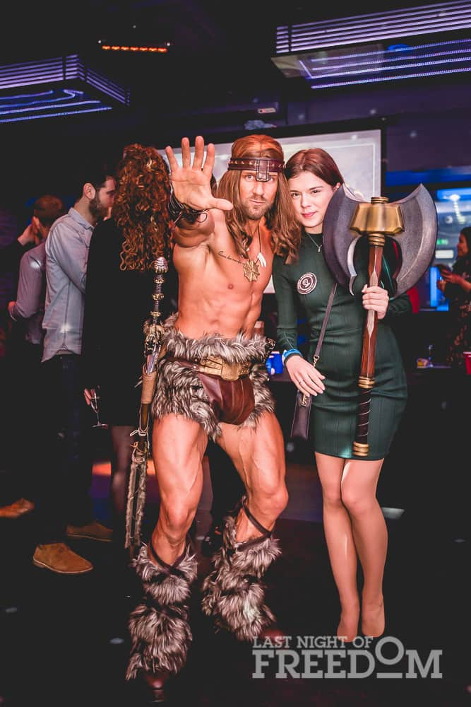 A man dressed as Conan the Barbarian, stood with a woman holding his axe