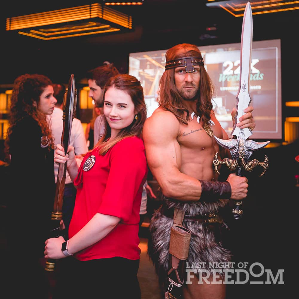 A man dressed as Conan the Barbarian, posing with a woman in a red top