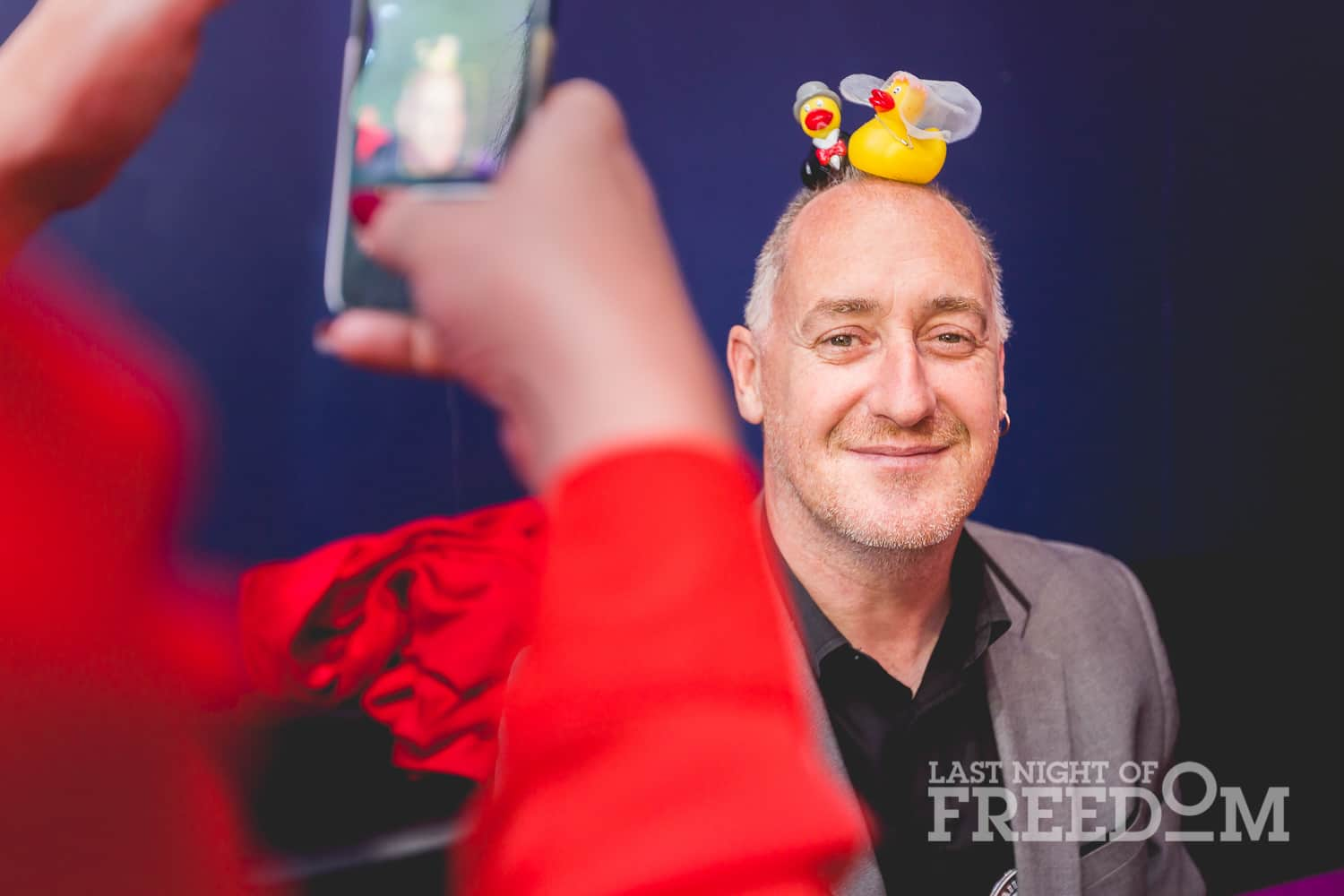 A woman's hands in the foreground, taking a picture of a man with two tiny ducks on his head