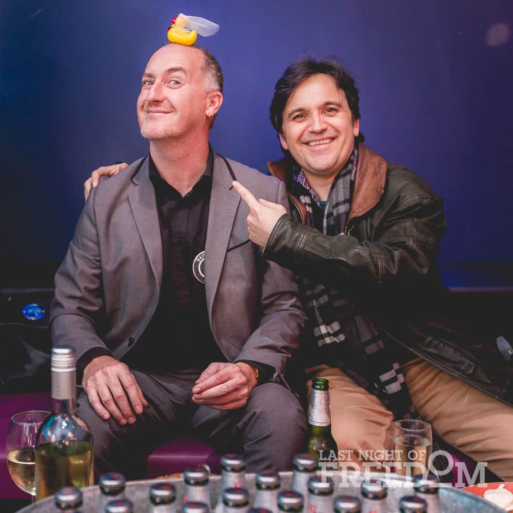 Two men posing for a photo, with one man balancing a yellow duck on his head