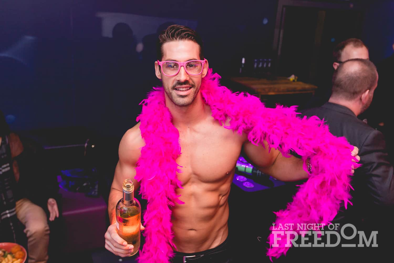 A semi-naked man posing with a pink boa around his neck
