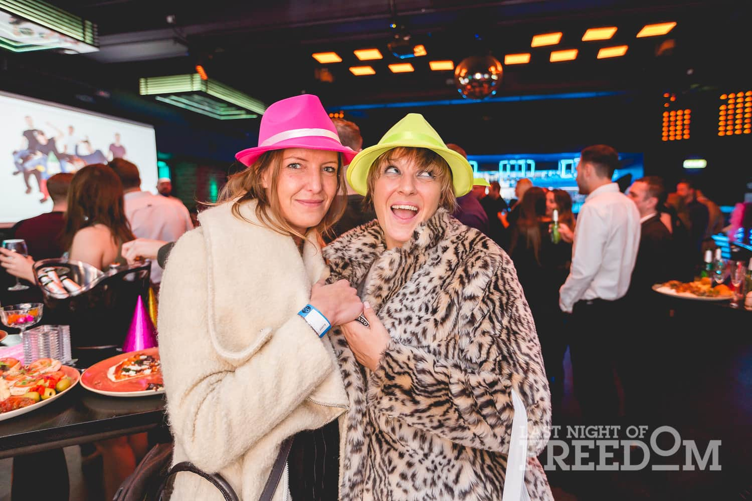 Two women posing in colourful hats and coats in a bar, with others in the background