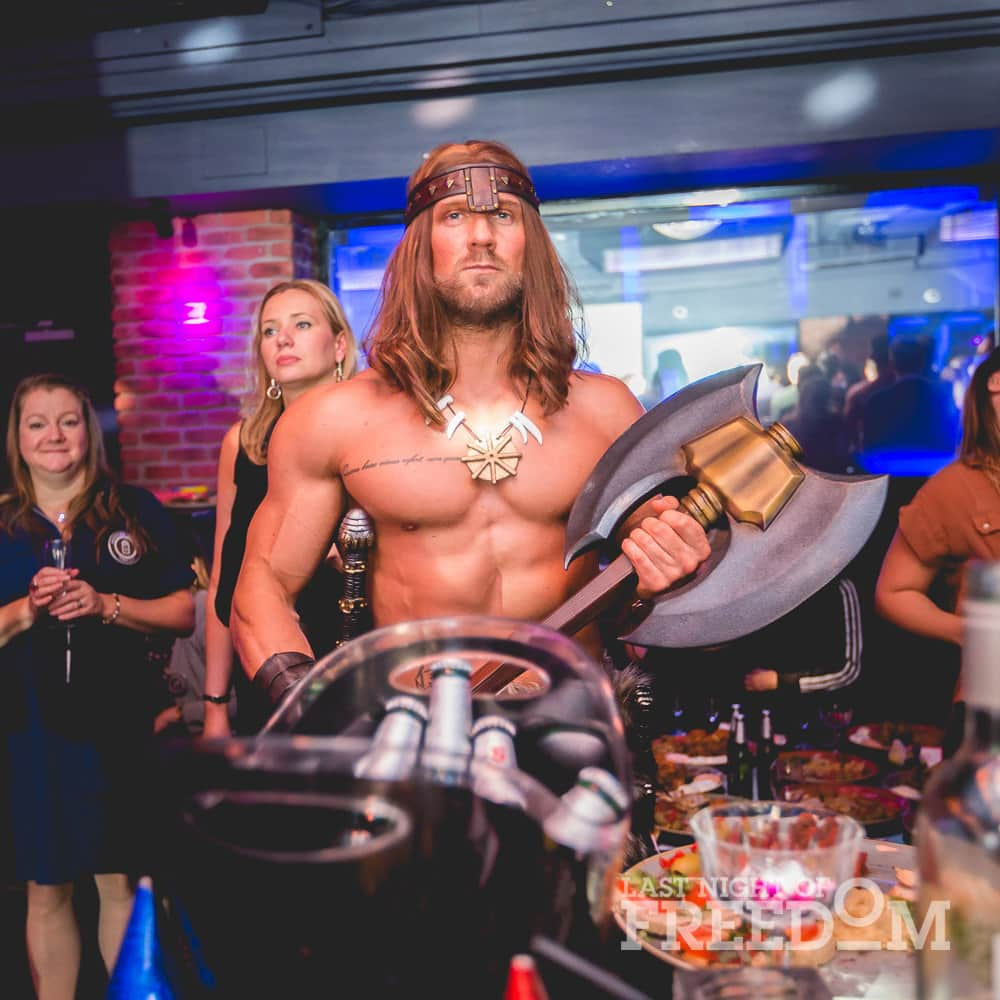 A man dressed as Conan the Barbarian, with two women in the background