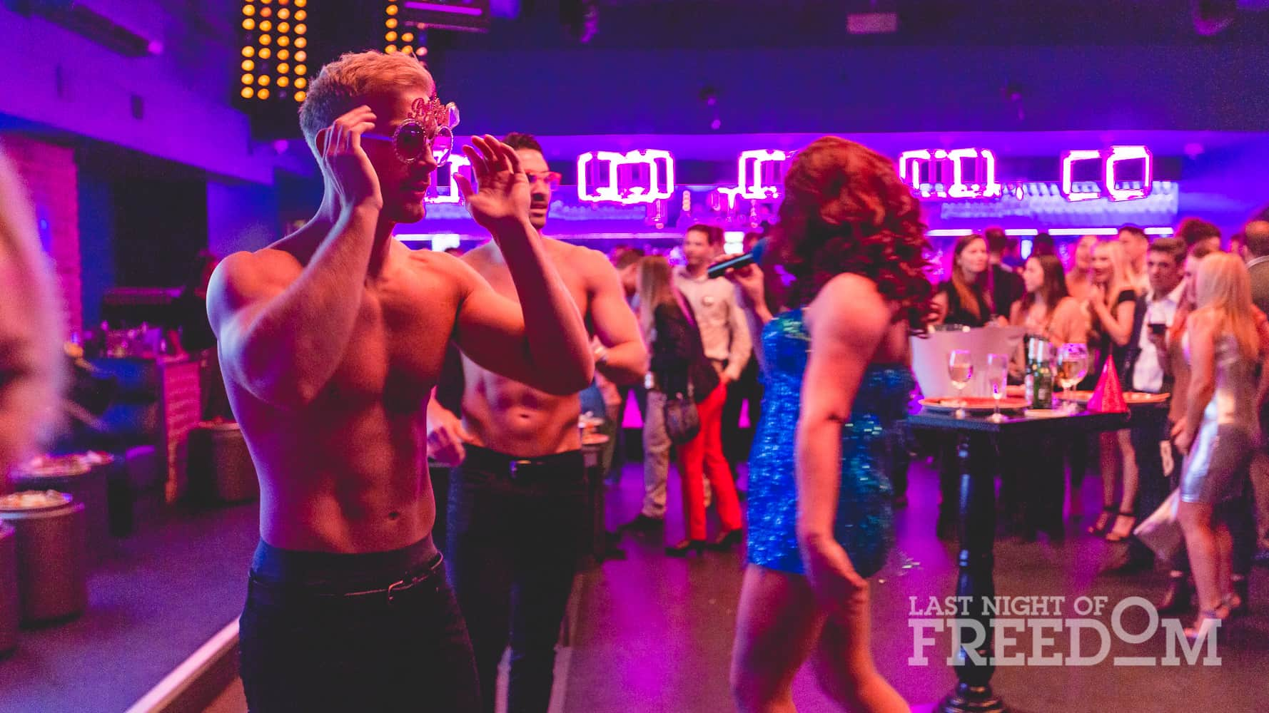 Two semi-naked men stood with a drag queen, with others in the background