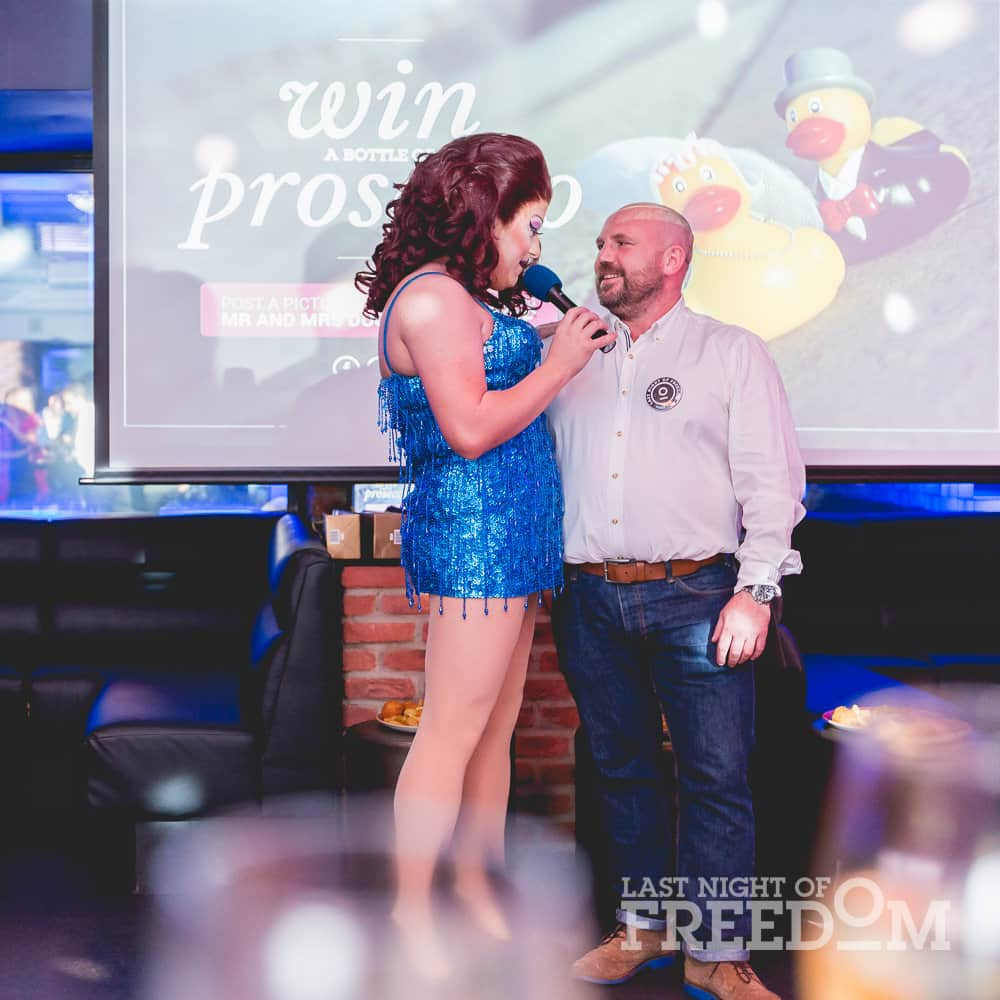 A man stood on stage with a drag queen