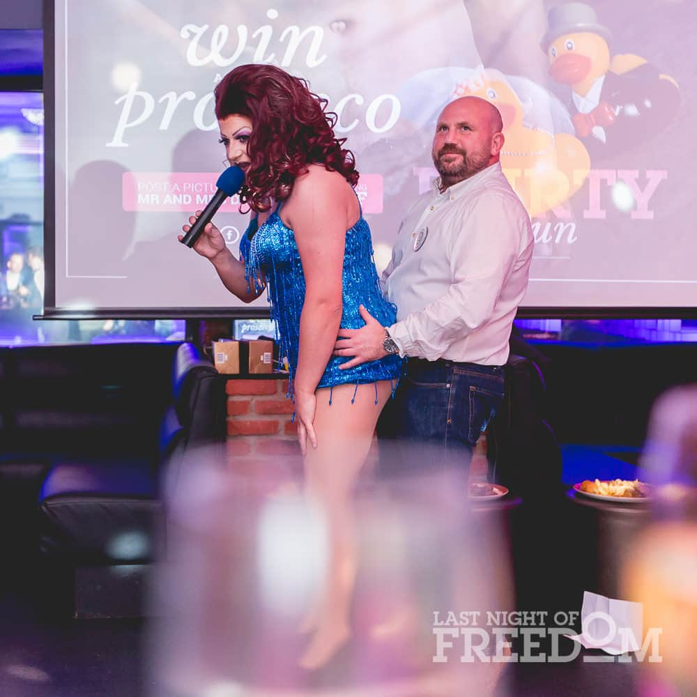 A man pretending to hump a drag queen on stage