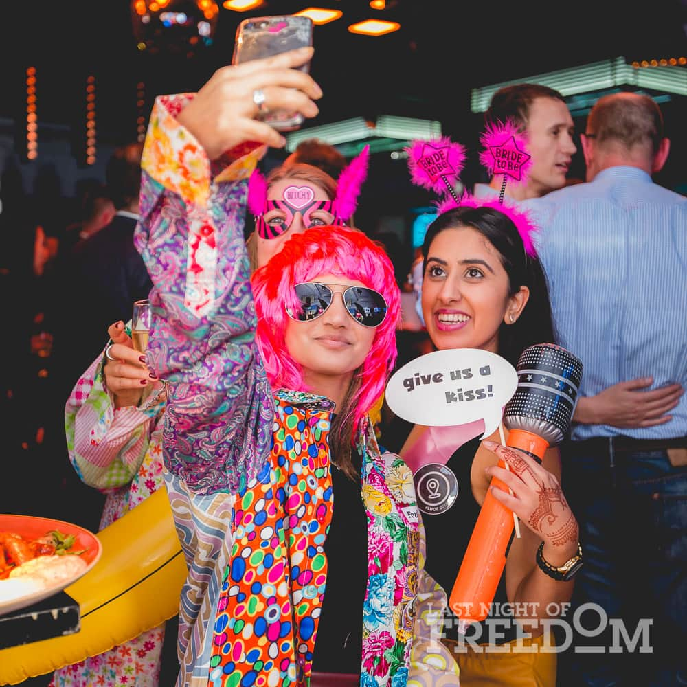 Three women taking a selfie with fun costumes and accessories