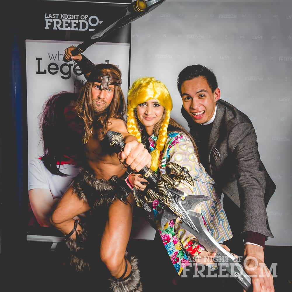 A man dressed as Conan the Barbarian, posing with another man and a woman in a blonde wig and floral coat