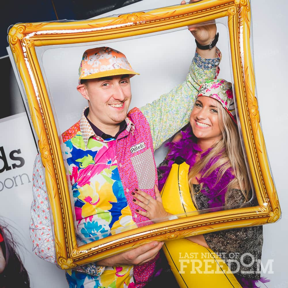A man woman posing in a photobooth with accessories and costumes, whilst holding a fake photo frame