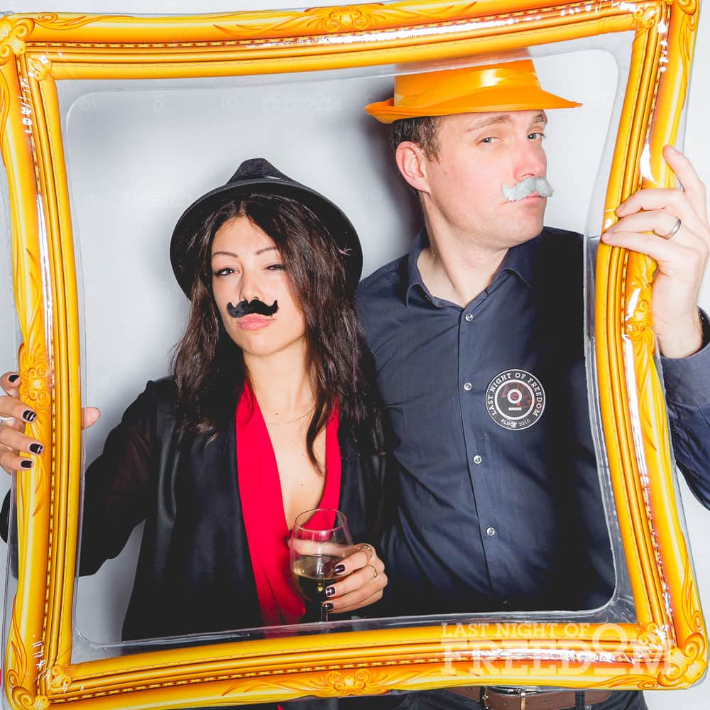 A man and woman posing in a photobooth, whilst holding a fake photo frame