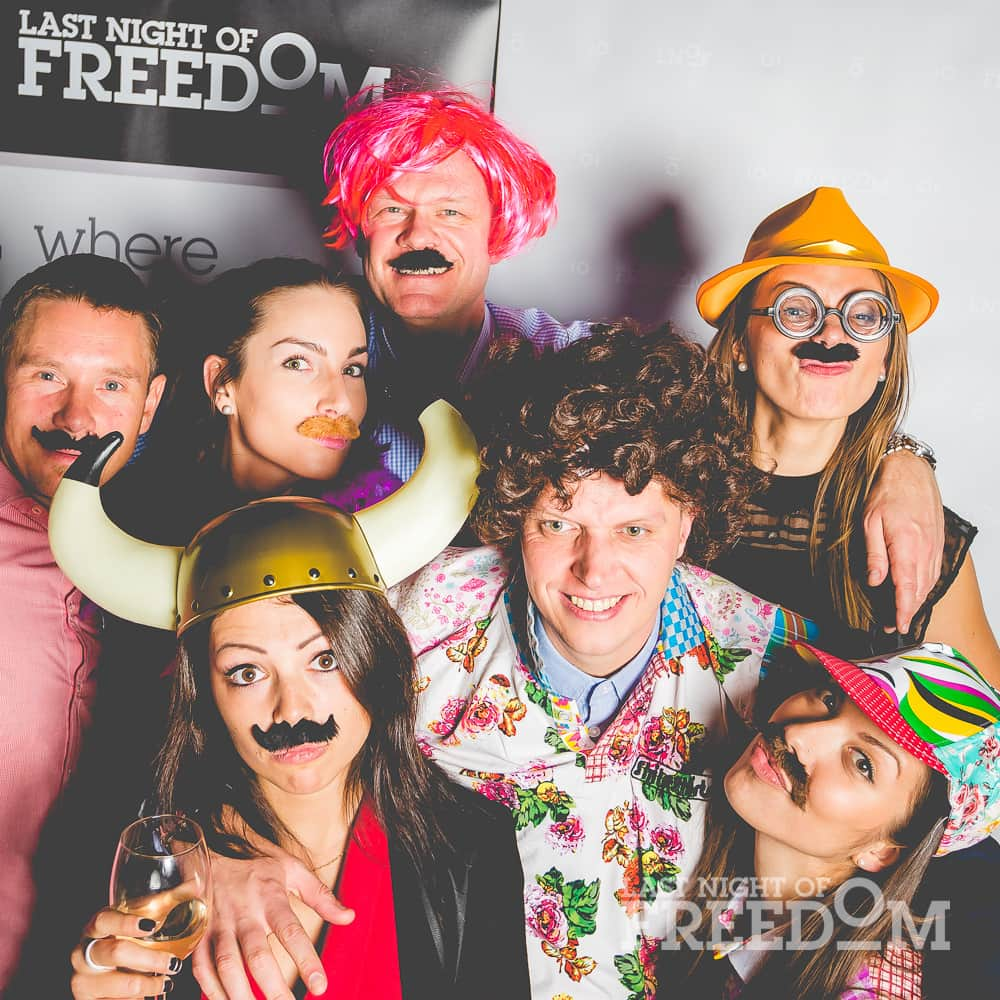A group of people posing in a photobooth, with costumes and accessories