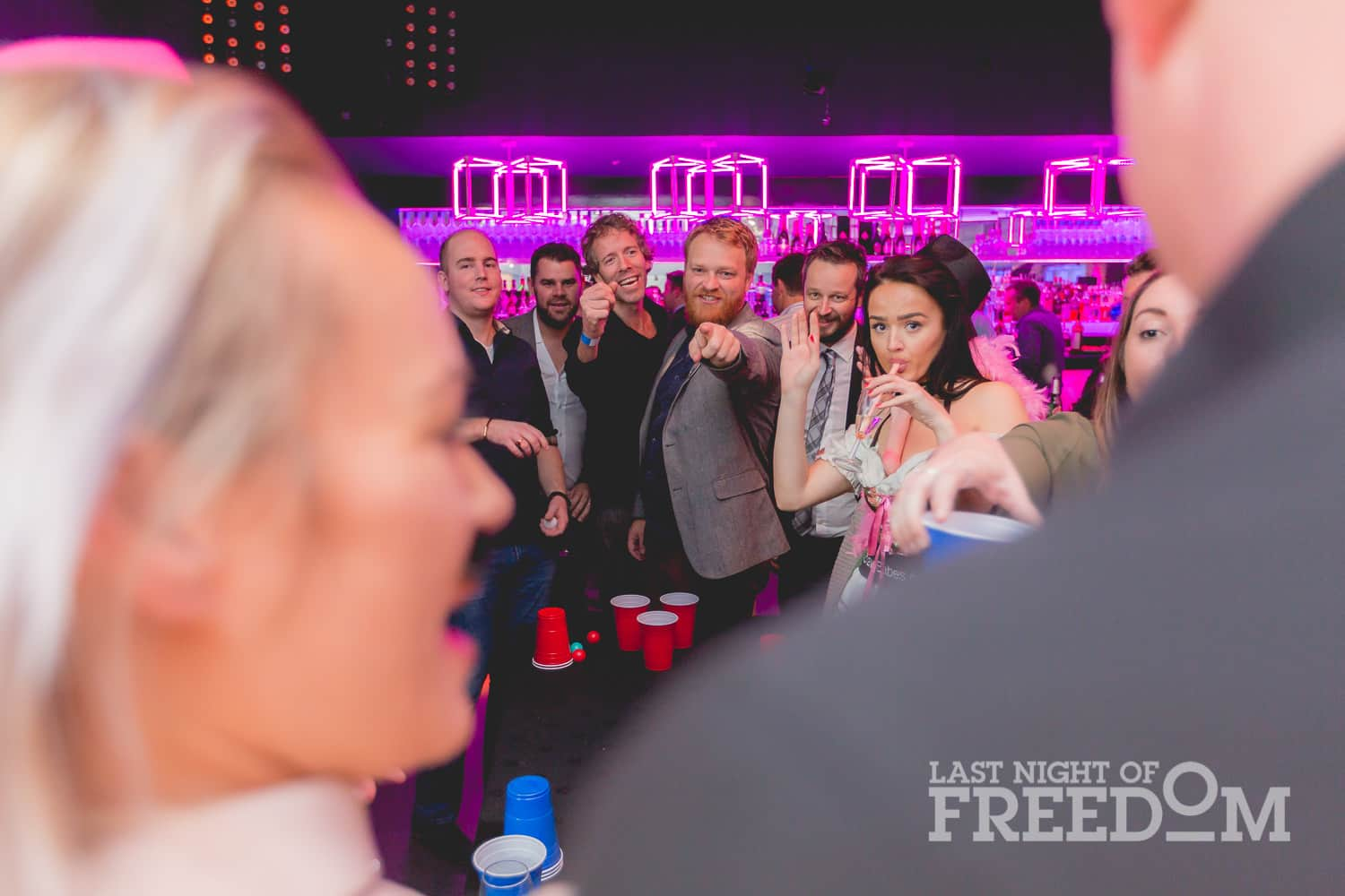 A shot through two people, showing people pointing and playing beer pong in a bar