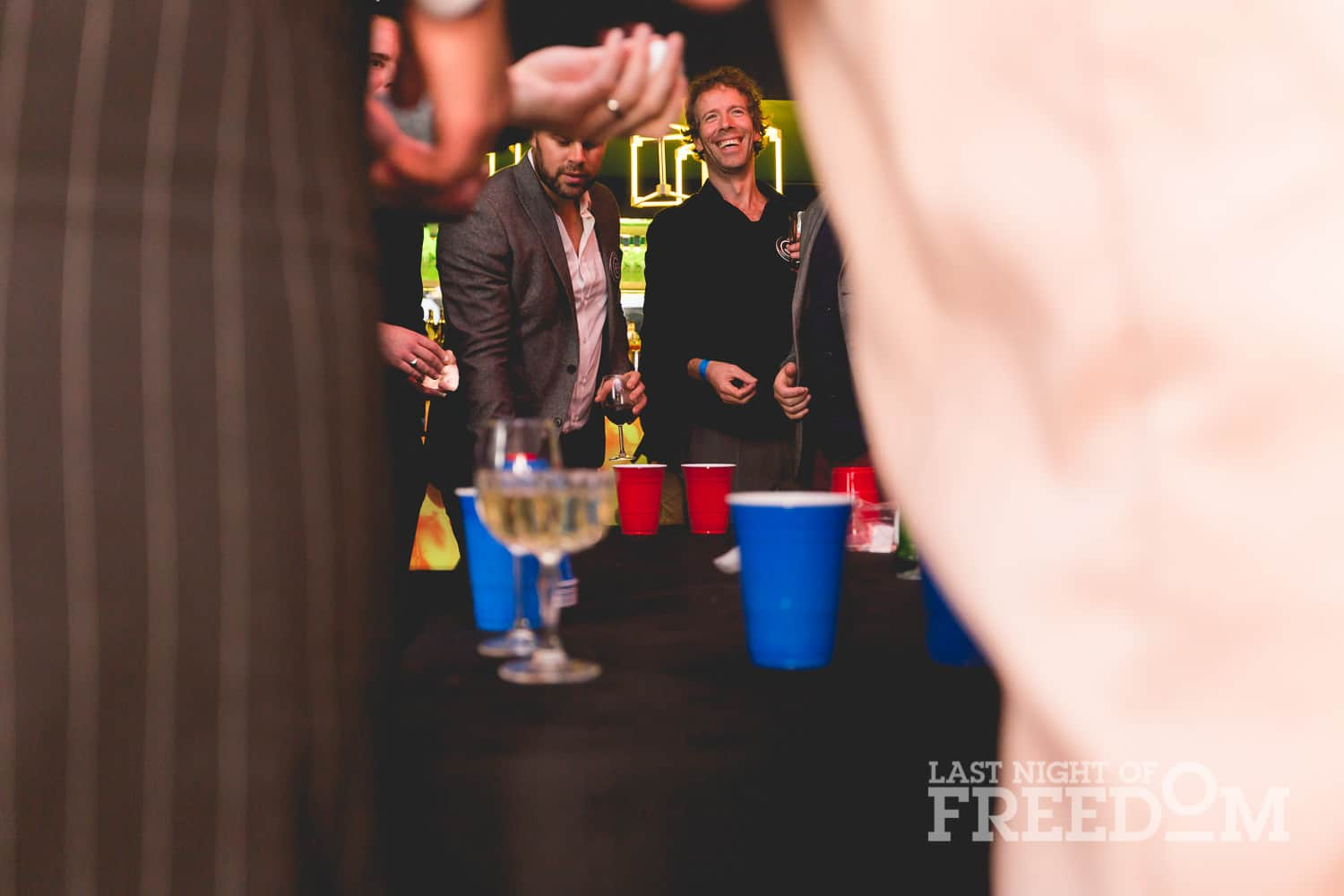 A shot through two people, showing men playing beer pong in a bar