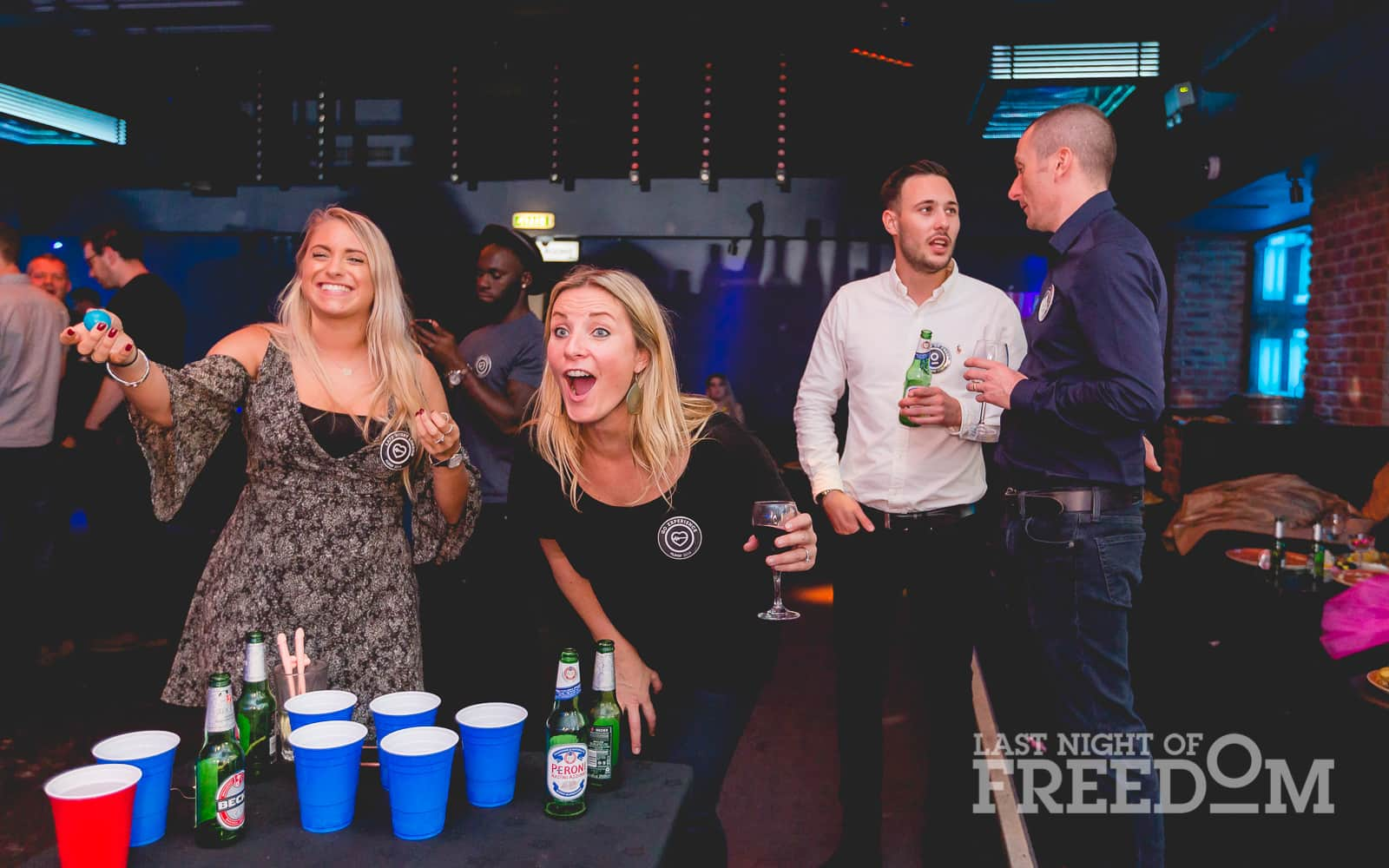Two women playing beer pong in a bar, with two men chatting in the background