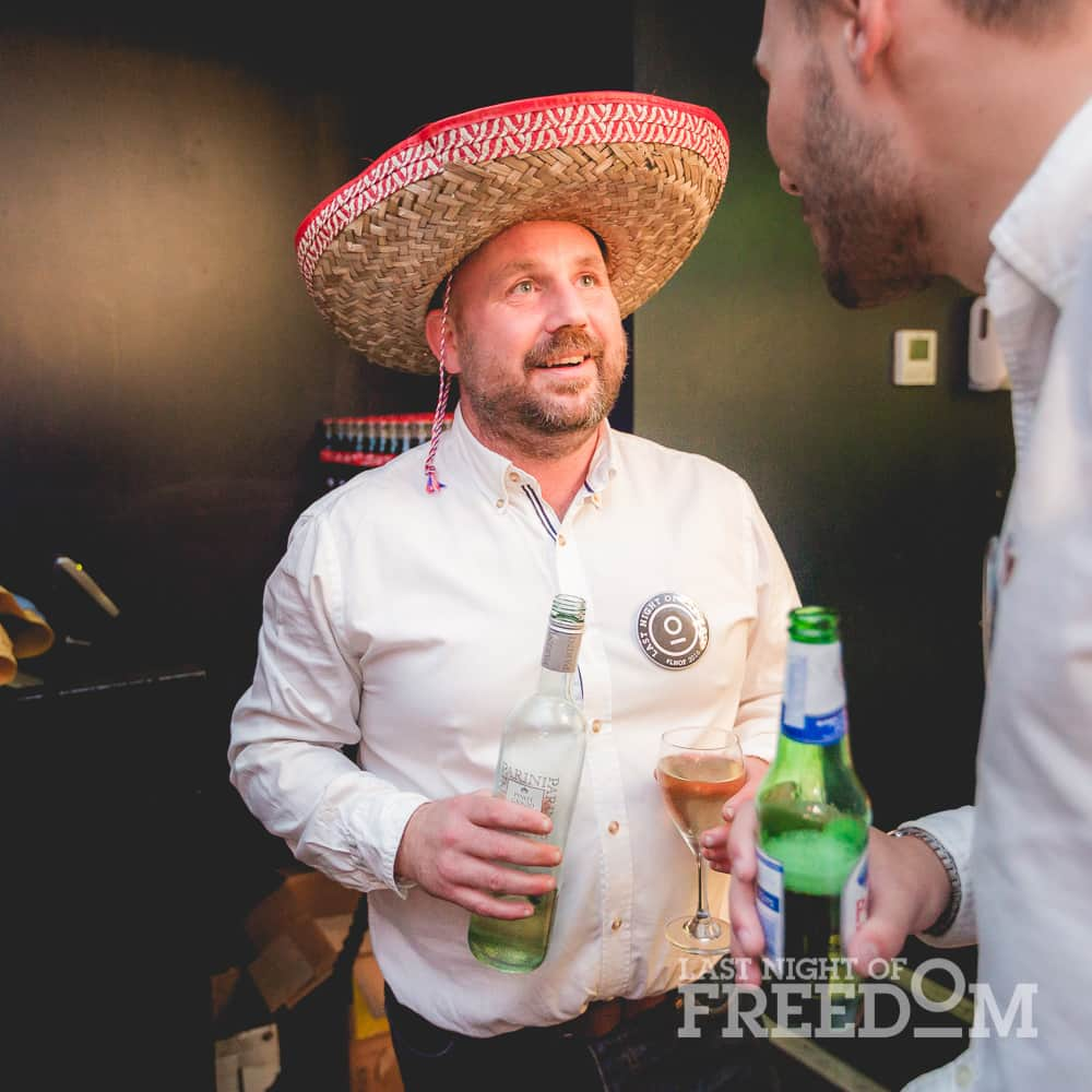 A man wearing a sombrero and holding a bottle and glass of white wine, chatting to another man