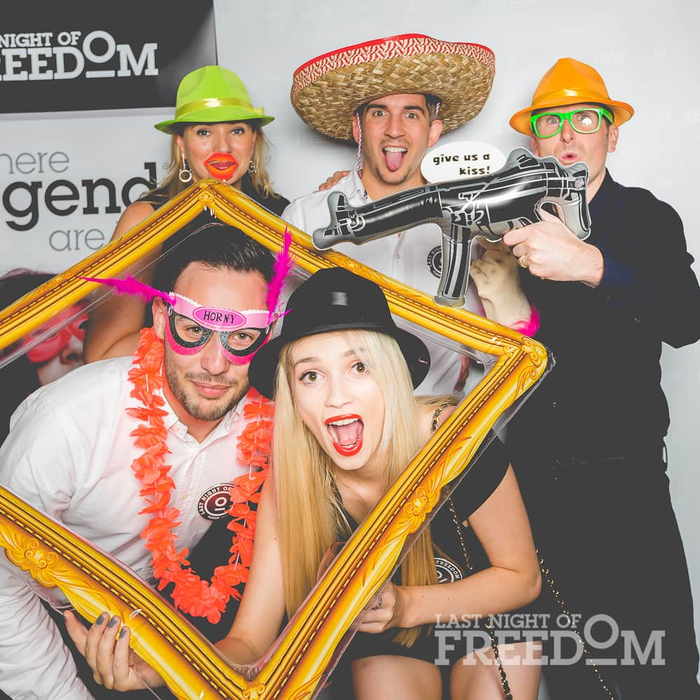 Men and women posing in a photobooth, with costumes, accessories and a fake photo frame