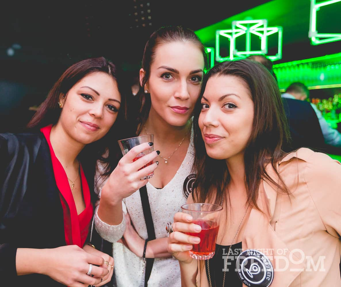 Three women posing for a picture and holding drinks