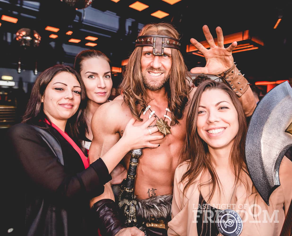 A man dressed as Conan the Barbarian and posing with three women