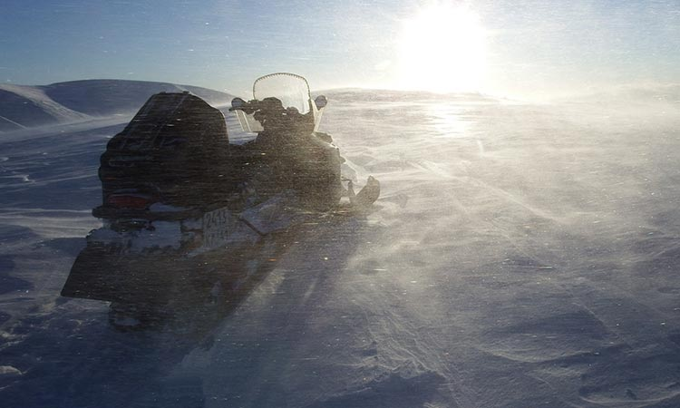 A snowbuggy on the snow with the sun in the background